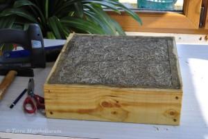 Pose de la toile métallique de type garde-manger pour terminer le coussin de la ruche Warré.