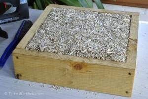 Remplissage du coussin de ruche Warré avec la chènevotte.